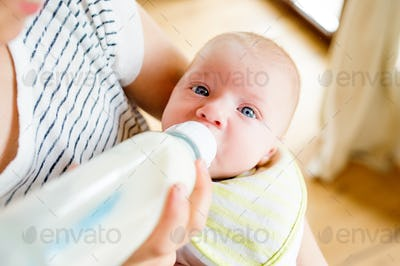 Unrecognizable mother feeding baby son, milk in bottle, close up