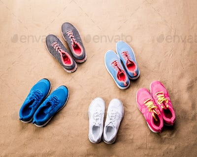 Various sports shoes laid on sand beach, studio shot