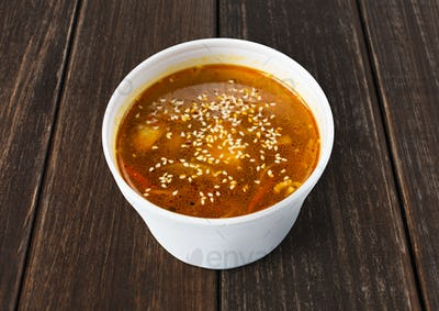Asian red fish soup with sesame closeup at blue wood