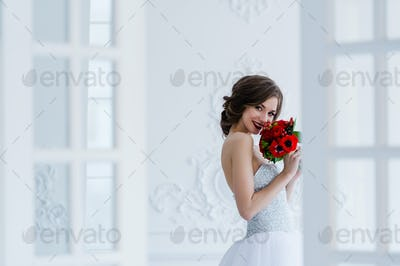 Fashion photo of a beautiful bride with flowers bouquet in her hands at the light room next to the