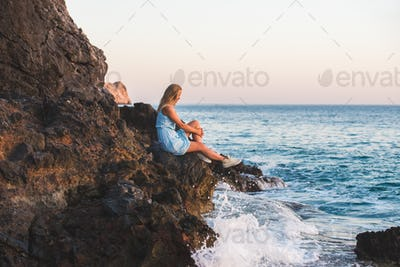 Young blond woman tourist in blue dress relaxing on stone rocks