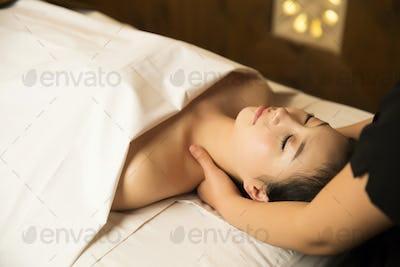 Portrait of Beautiful Asian Woman having relaxing massage in Spa