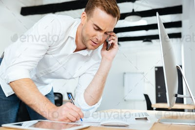 Businessman talking on cell phone and writing in office