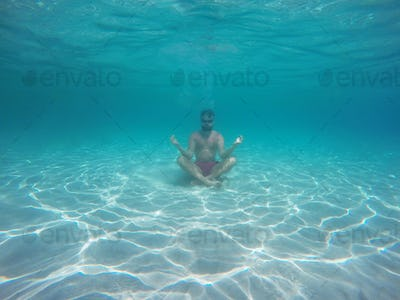Beard man with glasses in the lotus position meditating under wa