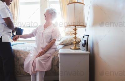 Nurse taking blood pressure of senior woman