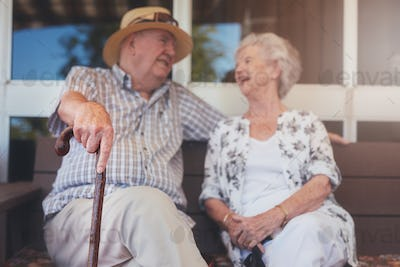 Loving elderly couple relaxing outdoors on a bench