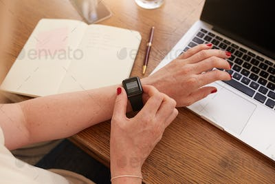 Woman at her work desk using smartwatch