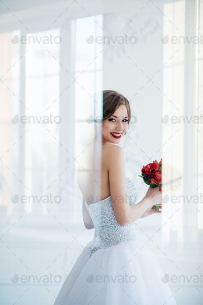 young and beautiful fashion art photo of a bride in white dress in living room. Shot through the