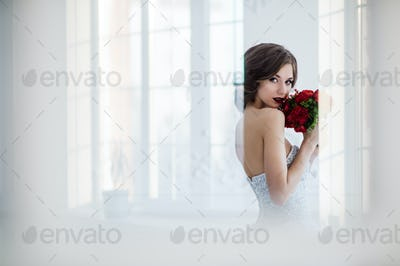 Glamorous young bride with flowers wearing wedding dress standing in front of doors indoors at