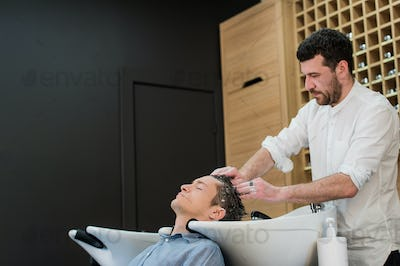 Young man at hairdresser salon getting his hair washed