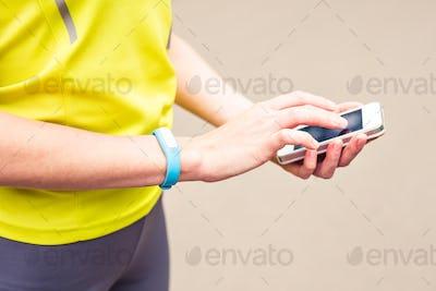 Woman using fitness bracelet during morning run