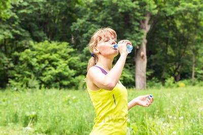 Fitness beautiful woman drinking water and sweating after exercising on summer hot day