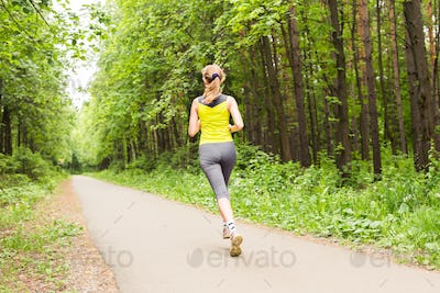 Young woman running outdoors in the park.