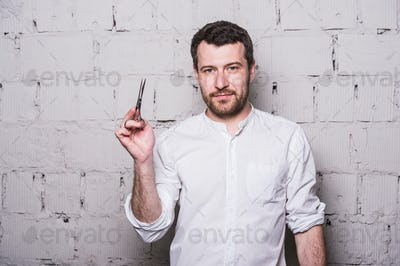 Portrait of young beautiful hairdresser man wearing white shirt with scissors on grey brick wall
