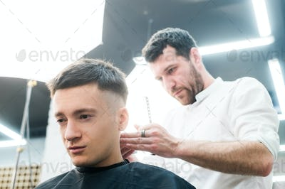 Professional styling. Close up side view of young man getting haircut by hairdresser with electric