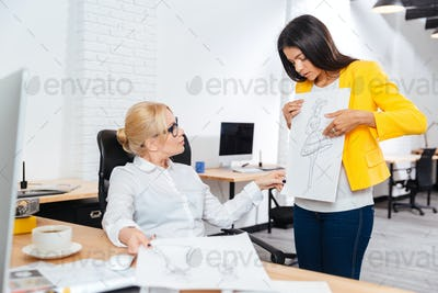 Team of two female architects discussing sketches at the office