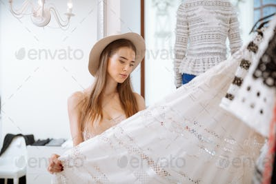 Pensive woman standing and choosing skirt in clothing store