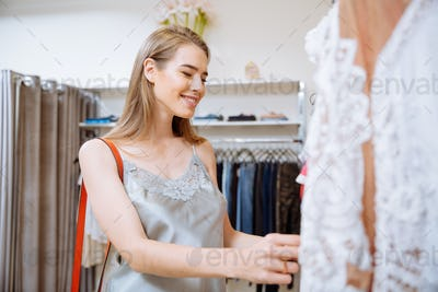 Cheerful young woman doing shopping in clothing store