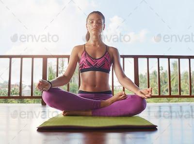 Beautiful female model meditating in lotus yoga pose