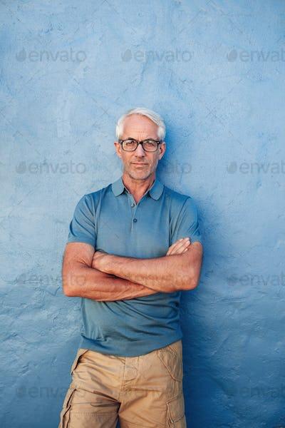 Confident mature man standing against a blue background