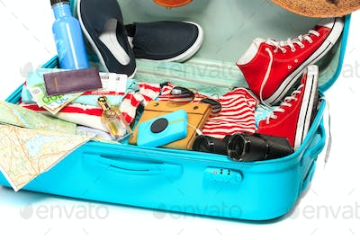 The open blue suitcase, sneakers, clothing, hat, and retro camera on white background.
