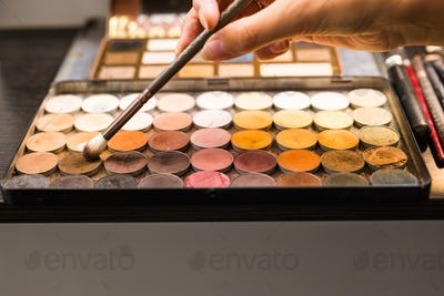 The female hands eyeshadow palette and cosmetic brush