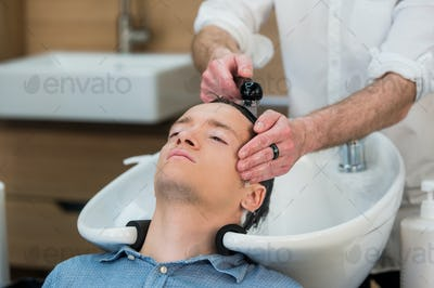 Close-up of a young man having his hair washed in hairdressing salon