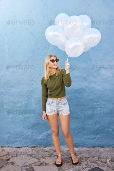 Attractive female fashion model holding balloons