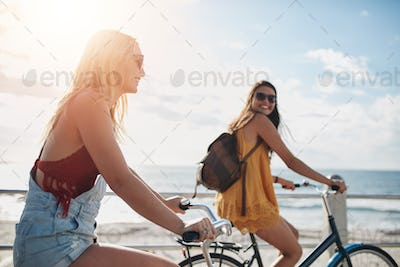 Two women going by bike on sunny day