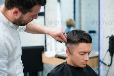 Portrait of handsome man with black hair having haircut at salon. Hairdresser holding comb and