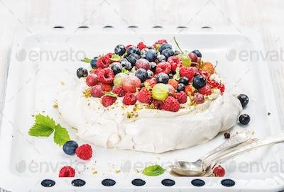 Homemade Pavlova cake with fresh garden and forest berries on white baking tray over light backdrop