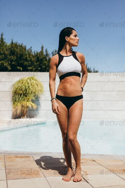 Slim young woman athlete at the poolside