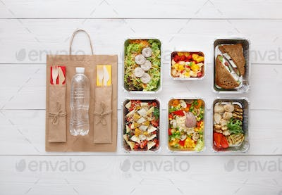 Healthy food take away in boxes, top view at wood