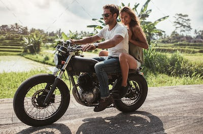 Young couple enjoying motorcycle ride on country road