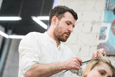 Hairdresser cutting client's hair in salon with electric razor closeup.