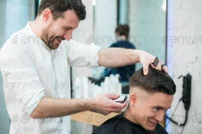 Professional styling. Close up side view of young satisfied man getting haircut by hairdresser with