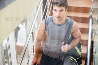 Sportsman with bag walking on training in gym
