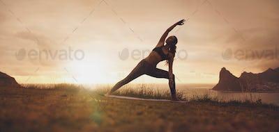 Utthita Parsvakonasana yoga asana on the cliff at sunset