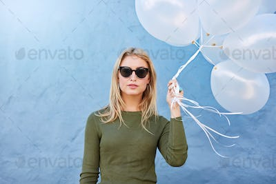 Stylish young woman with white balloons