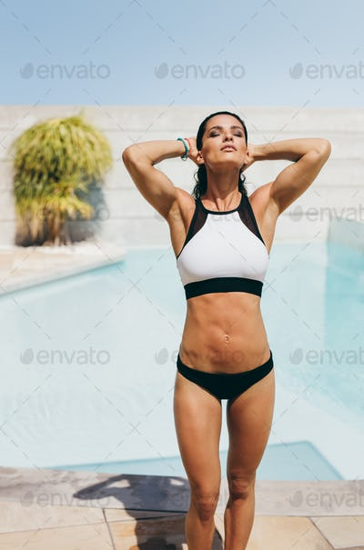 Young female athlete in swimwear standing at poolside