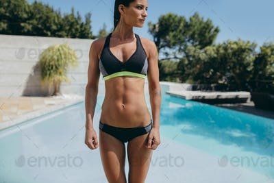 Woman in sports lingerie standing near swimming pool