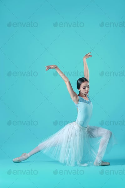 Ballerina in white dress posing on toes, studio background.