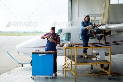 Engineers repairing airplane