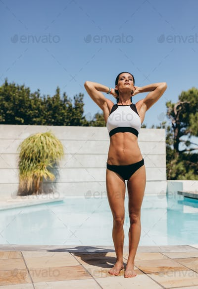 Slim and fit young woman in swimwear at the poolside