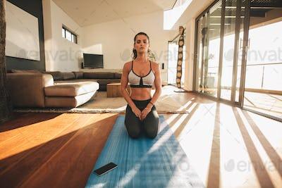 Young woman practicing yoga indoors, Vajrasana.