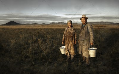 Mongolian Couple Farmers Holding Basin And Posing In The Field