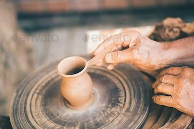 Potter sculpts a clay pot
