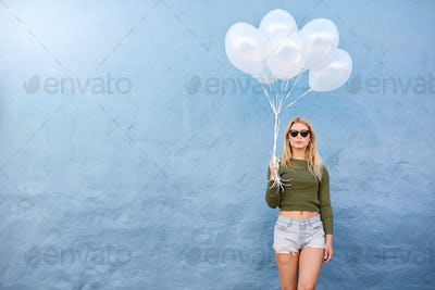 Attractive female fashion model with balloons