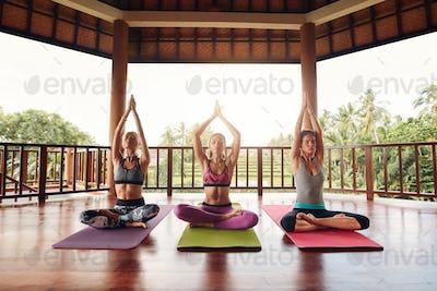 Three women meditating in yoga class
