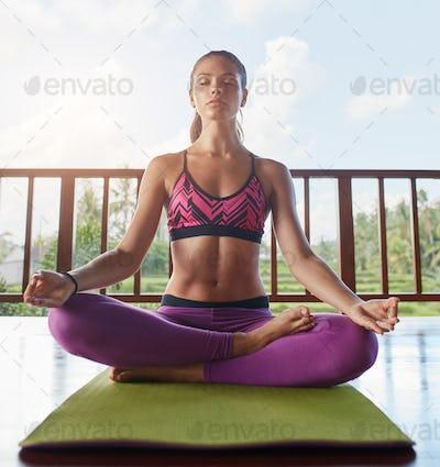 Young woman meditating at yoga class